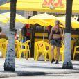 Adriana Esteves caminha de top e short em orla de praia de São Conrado