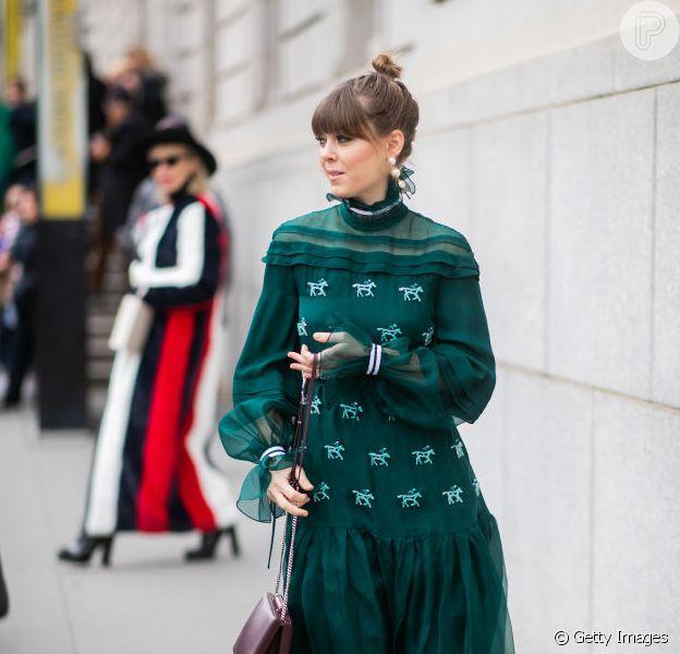 Vestido verde-esmeralda com bordados combinado a botas brancas e bolsa grená