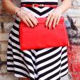 Combine a bolsa vermelha com peças de tons neutros, como o vestido ou a saia em preto e branco