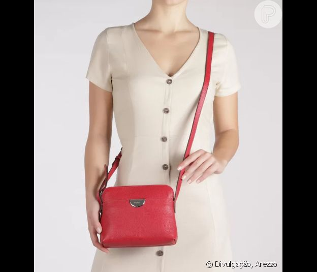 A bolsa vermelha, com alça tiracolo, traz o mood do Natal ao look