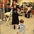 Bruna Hamú se diverte ao perceber as brincadeiras do filho diante dos fotógrafos