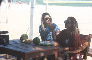 Ticiane Pinheiro bebe água de coco e come sanduíche durante gravação na praia