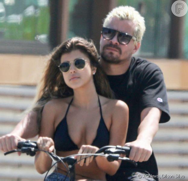 Thiago Martins carrega namorada, Talita Nogueira, em bicicleta durante passeio na orla da praia