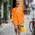 O blazer laranja deixa o look com tênis bem fashionista