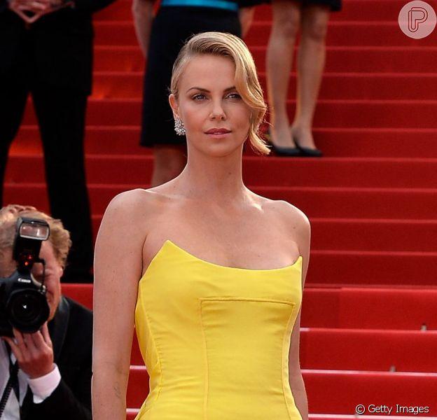 Charlize Theron escolheu um vestido tomara que caia amarelo, da Dior, para o segundo dia do Festival de Cannes 2015, nesta quinta-feira, 14 de maio de 2015