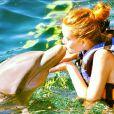 Marina Ruy Barbosa faz um coque para beijar um golfinho