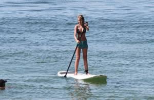 Luiza Brunet caminha enquanto a filha, Yasmin, pratica stand up paddle no Rio
