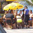 Gaby Amarantos e César Menotti sentam em um quiosque de Ipanema, no Rio, após jogarem tênis de praia