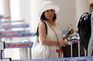 Regina Duarte, de chapéu e óculos escuros, faz foto com fã em aeroporto do Rio