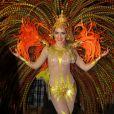 Monique Alfradique samba com fantasia que representa o Sol no desfile pela Grande Rio