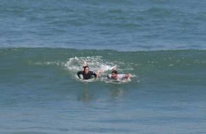 Juliano Cazarré surfa com a mulher e troca beijos na praia da Macumba, no Rio