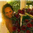 Paola de Luca no dia de seu aniversário, com três buquês de rosas vermelhas