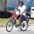 Filha de Deborah Secco e Hugo Moura, Maria Flor sentou na cadeirinha da frente da bicicleta do pai