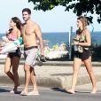 Namorada de Cauã Reymond, Mariana Goldfarb caminha com amigos na praia da Barra da Tijuca