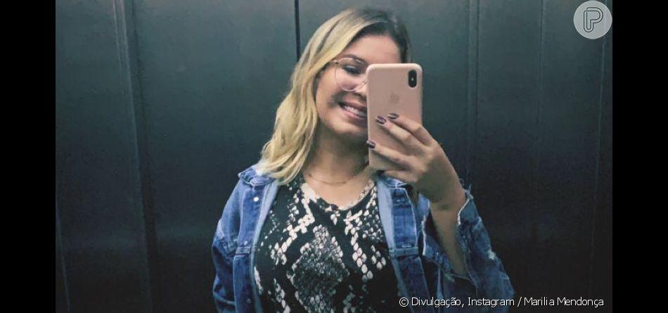 Marilia Mendonça combinou destroyed jeans com baby look com estampa de cobra