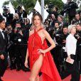 Alessandra Ambrosio elegeu vestido vermelho com fenda gigante na lateral e capa