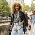 Moda streetwear: camiseta descontraída com estampa de banda pode ser combinada à calça jeans com recortes e jaqueta de couro para look fashionista