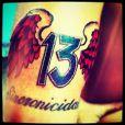 Na parte externa do braço, o ator tem o número 13 com asas e a palavra 'Sincronicidade'