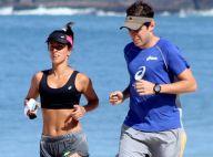 Carol Barcellos mostra barriga sequinha durante corrida na praia com o marido