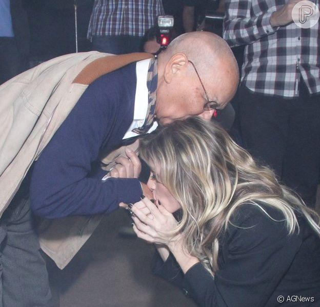 Amora Mautner se ajoelha e beija as mãos de Nelson Xavier durante festa de lançamento de 'Joia Rara'